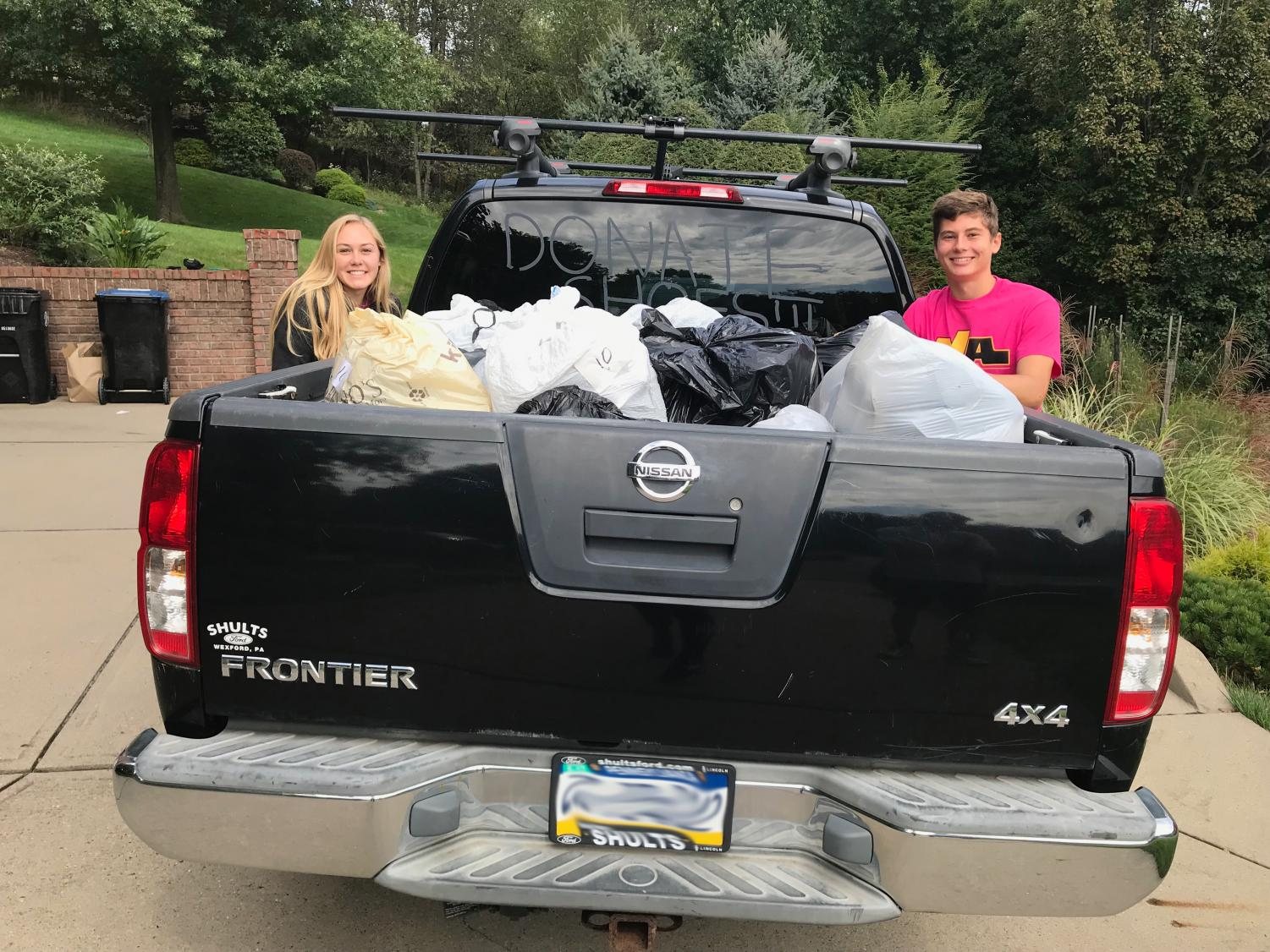 NAXC's Kelsey Hudson and Luke Turkovich stand beside Hudson's truck-full of shoes to be donated around the world.