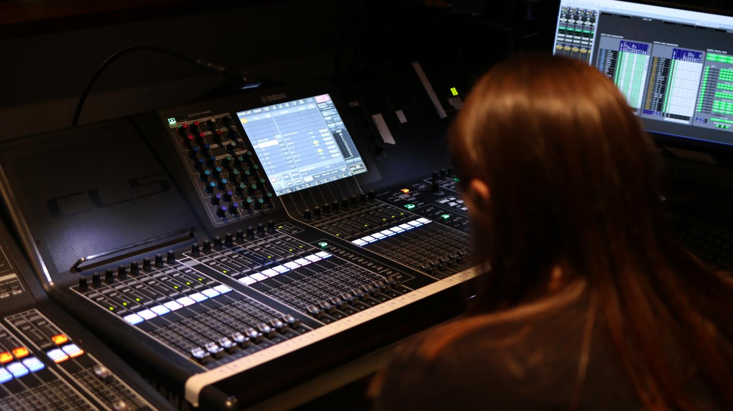 Macy Rothermel sits at the sound board in the auditorium booth during a tech week rehearsal.