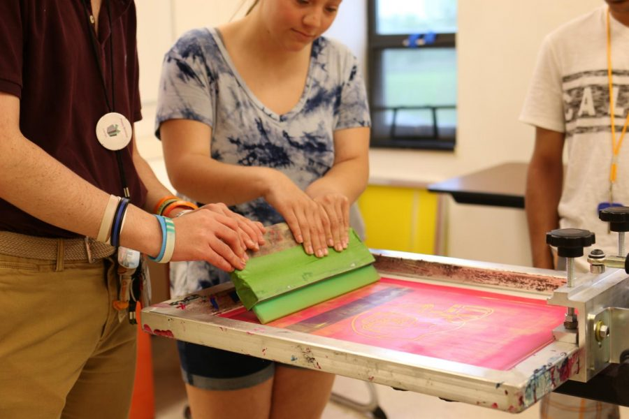 Students+in+the+Tiger+Shop+prepare+the+press+for+a+t-shirt+printing.