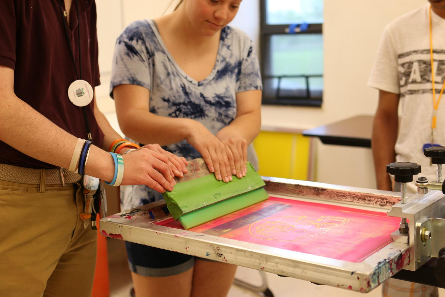 Students in the Tiger Shop prepare the press for a t-shirt printing.