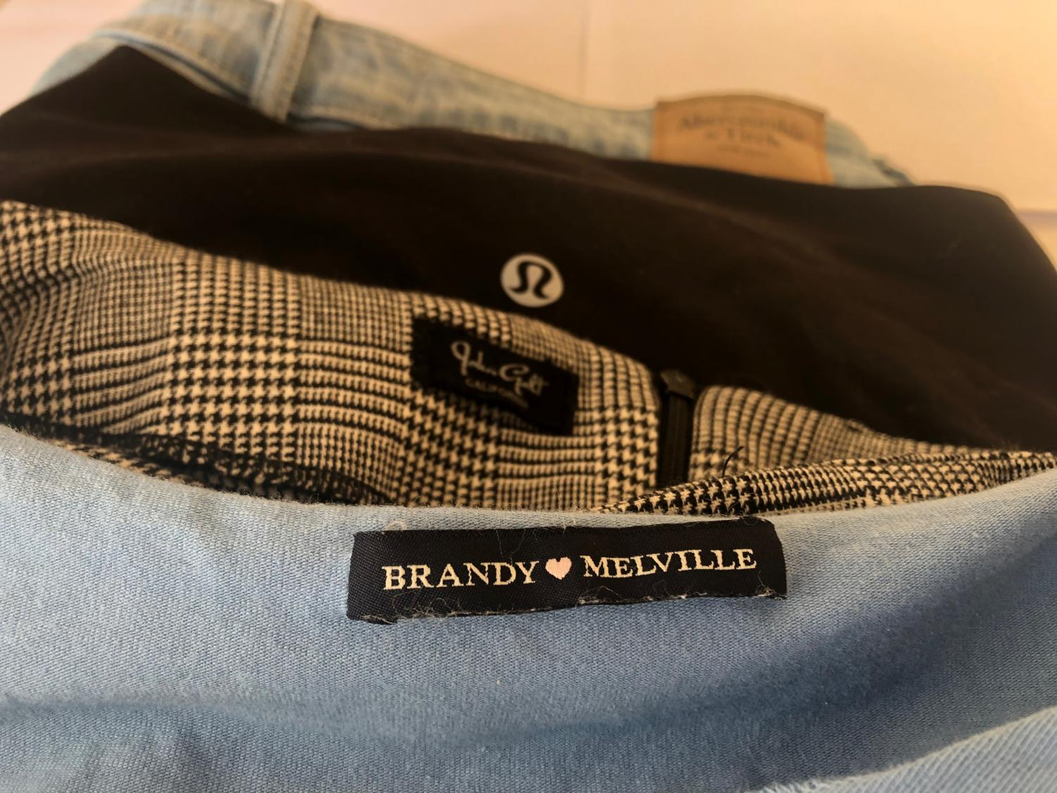 Clothing tags of popular brands that have limited or one size fits all clothing.