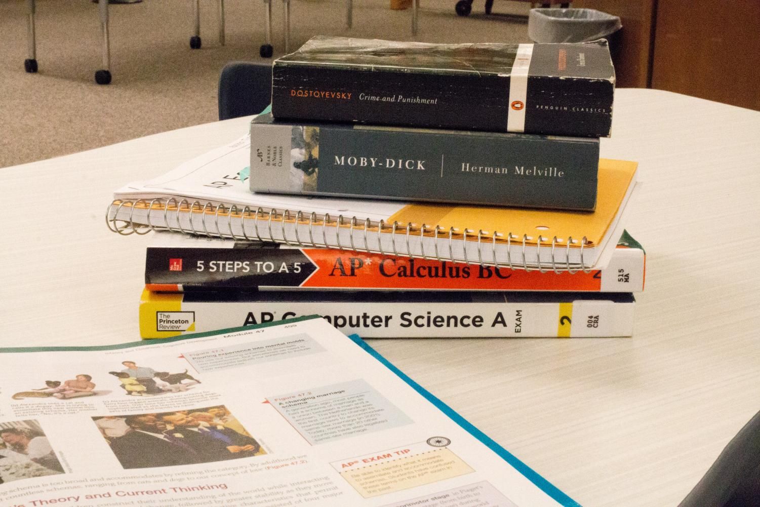 AP book open with other school materials stacked on a desk
