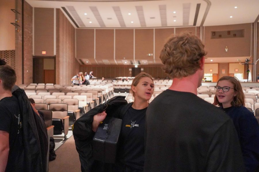 Emilie Whitewolf and Amy Hendricks talk to Logan Henderson while waiting in line to return uniforms.