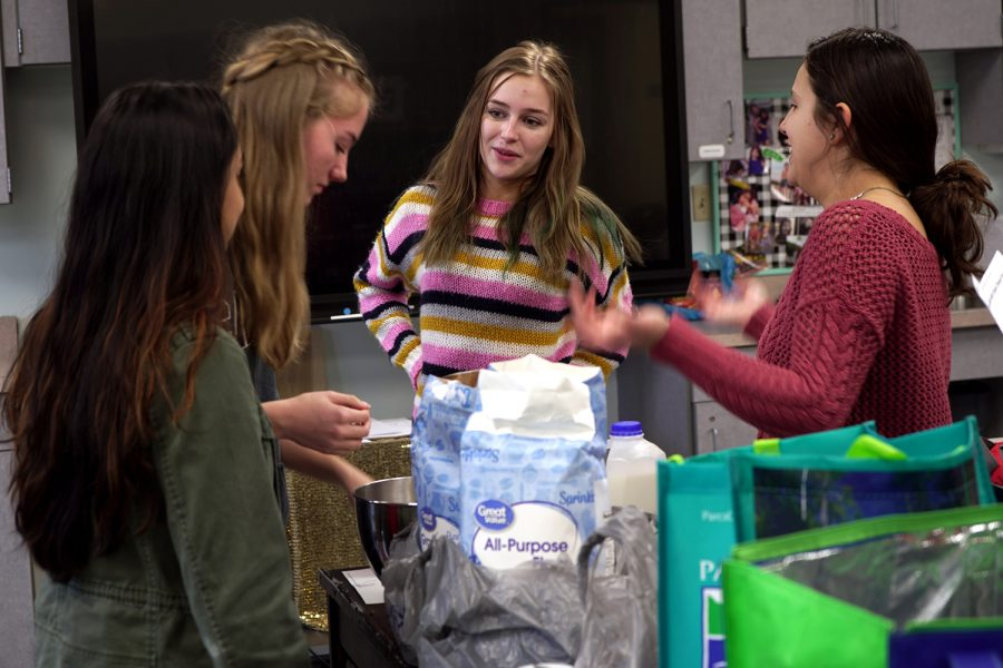 Ashna Patel, Lena Voss, Carsyn Nash, and founder Ana Key gathering ingredients to bake some treats for a good cause.