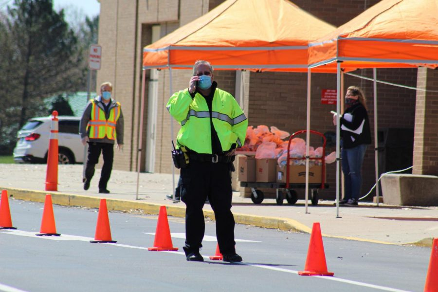 NASH School Resource Officer Todd Ray prepares to direct traffic as the Food Services and volunteer staff organize meal distribution.