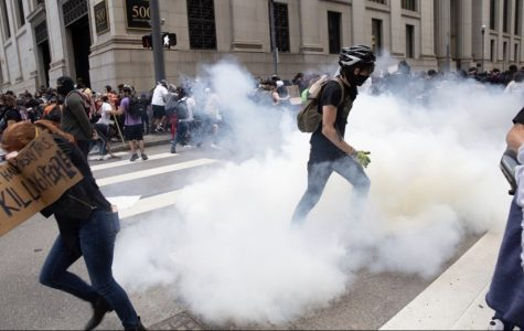 Protesters flee as tear gas canisters are released among the crowd.