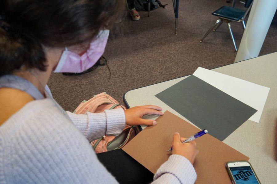Sophia Elliott works on a design for a classroom bulletin board.