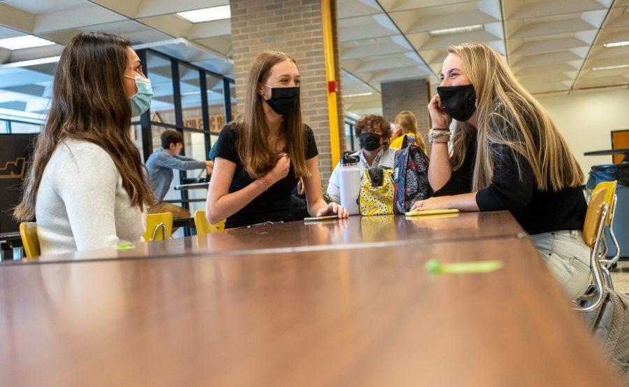 Sonia Lofgren, Ana Donaldson, and Liza Lowman sit six feet apart during their lunch period.