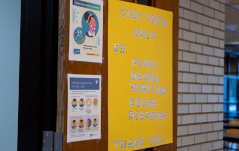 The door to the nurse's office is decorated with informational posters about the coronavirus.