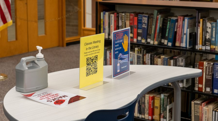 Social distancing signs and bottles of hand sanitizer throughout the library remind students just how different this school year is.