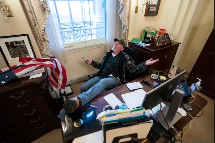 Richard Barnett from Arkansas sits at Speaker of the House Nancy Pelosi's desk after the breach of Capitol Hill