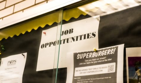 Job postings hung up in the NASH Cafeteria trophy display.