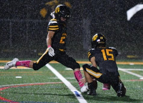 Harron Lee kicks a field goal in the rain during a home Pink Out game